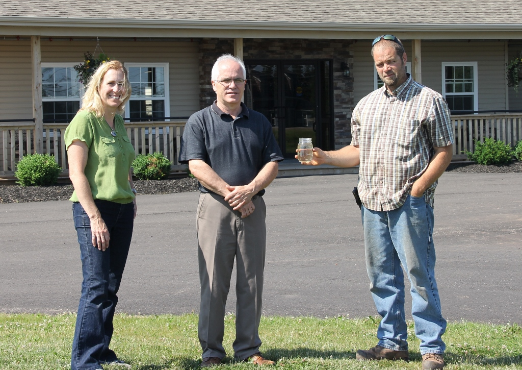 Kelly Galloway with Owner, Alan MacPhee, and septic installer,  Philip Clark (holding bottle of clear effluent)
